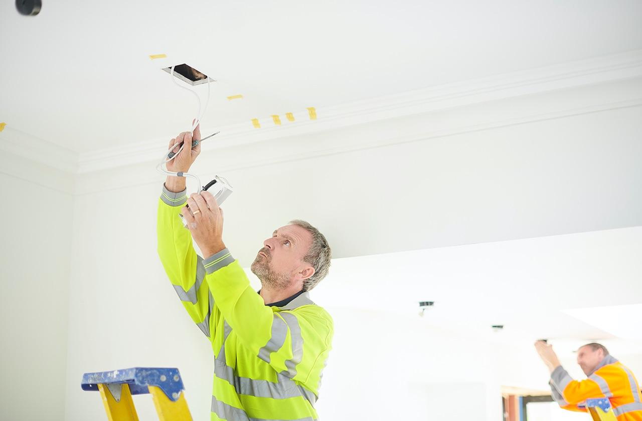 Electrician working on ceiling speaker