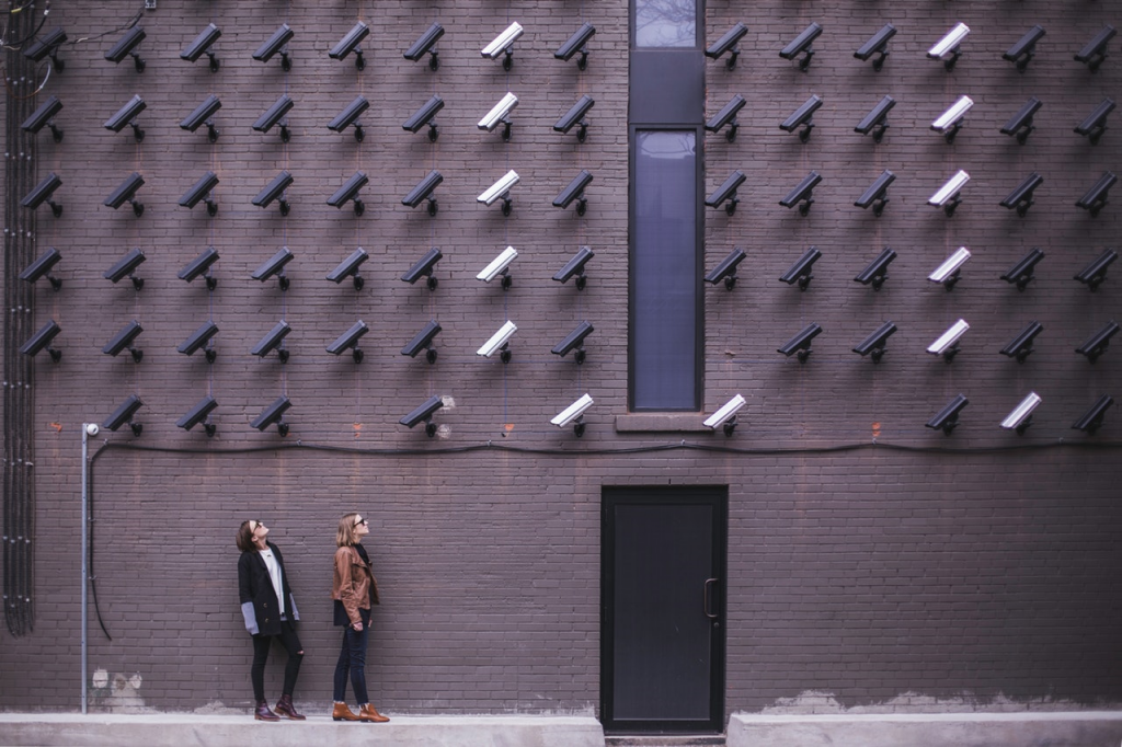 Two pedestrians looking up at art display of CCTV cameras